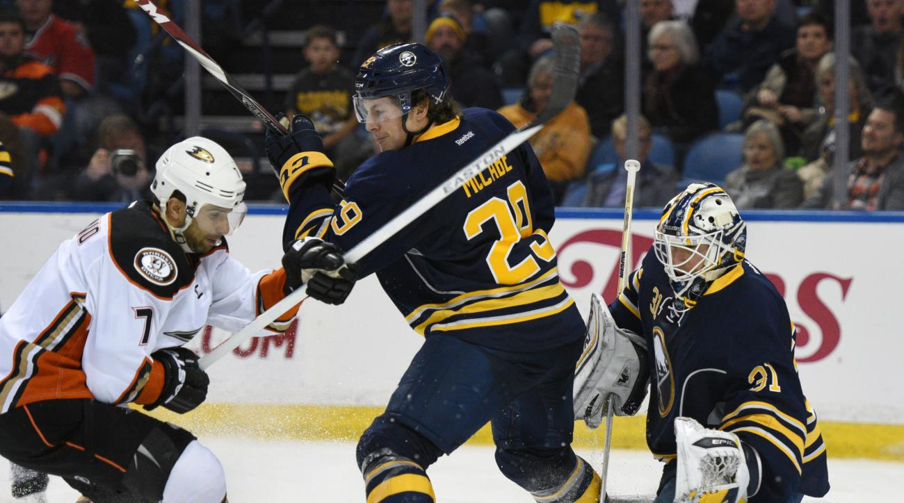 Anaheim Ducks left winger Andrew Cogliano (7) battles for the puck with Buffalo Sabres defenseman Jake McCabe (29) as goaltender Chad Johnson (31) defends during the second period of an NHL hockey game, Thursday Dec. 17, 2015 in Buffalo, N.Y. (AP Photo/Ga