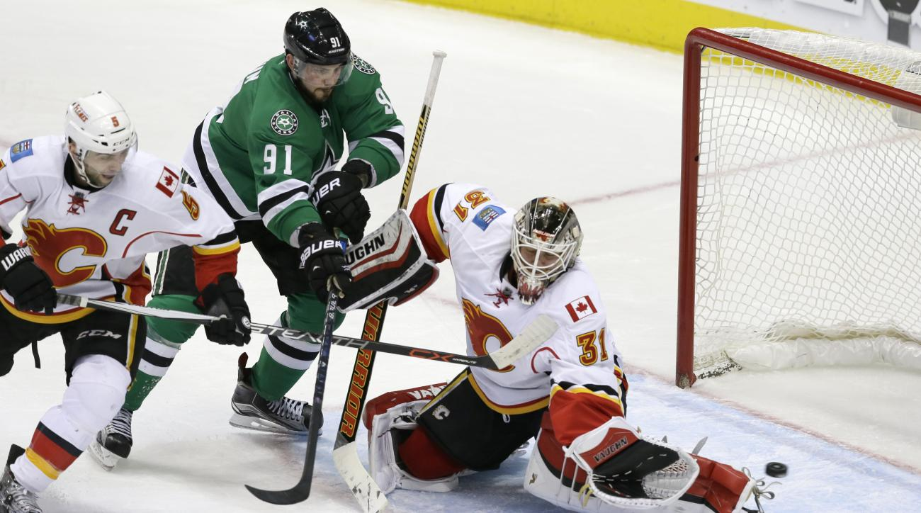 Calgary Flames goalie Karri Ramo (31) and defenseman Mark Giordano (5) defend the goal against Dallas Stars center Tyler Seguin (91) during the second period of an NHL hockey game Thursday, Dec. 17, 2015, in Dallas. The Flames won 3-1. (AP Photo/LM Otero)