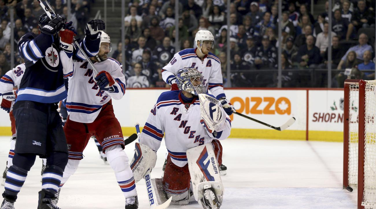Winnipeg Jets' Andrew Ladd (16)battles with New York Rangers' Dan Boyle (22) as a shot by Tyler Myers, not seen, gets past goaltender Henrik Lundqvist (30) during the second period of an NHL hockey game Friday, Dec. 18, 2015, in Winnipeg, Manitoba. (Trevo