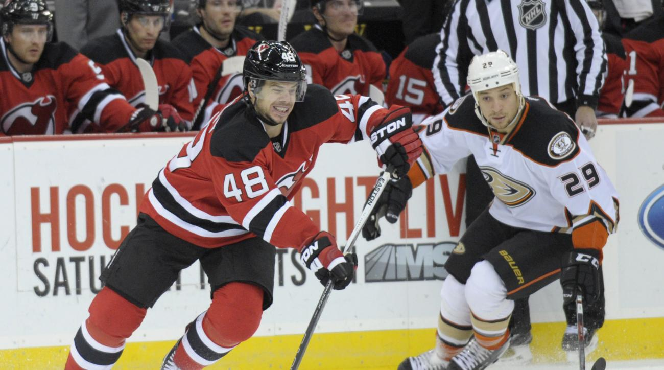 New Jersey Devils' Tyler Kennedy (48) moves the puck as Anaheim Ducks' Chris Stewart trails the play during the first period of an NHL hockey game Saturday, Dec. 19, 2015, in Newark, N.J. (AP Photo/Bill Kostroun)