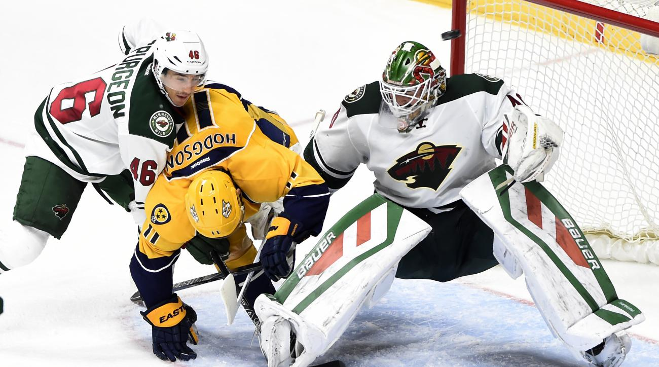 Minnesota Wild defenseman Jared Spurgeon (46) collides with Nashville Predators center Cody Hodgson (11) as Wild goalie Devan Dubnyk (40) deflects a shot above in the third period of an NHL hockey game Saturday, Dec. 19, 2015, in Nashville, Tenn. The Pred
