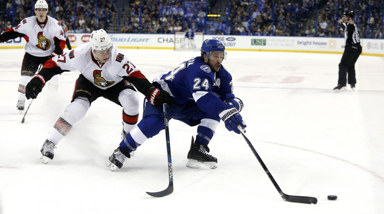 Tampa Bay Lightning right wing Ryan Callahan (24) and Ottawa Senators right wing Curtis Lazar (27) battle for the puck during the second period of an NHL hockey game, Sunday, Dec. 20, 2015, in Tampa, Fla. (AP Photo/Brian Blanco)