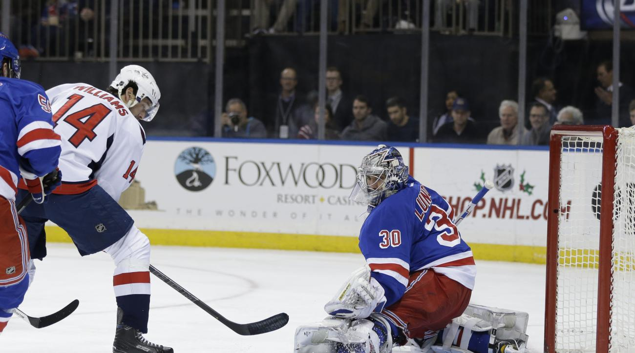 Washington Capitals' Justin Williams, left, scores on New York Rangers goalie Henrik Lundqvist during the first period of the NHL hockey game, Sunday, Dec. 20, 2015, in New York. (AP Photo/Seth Wenig)