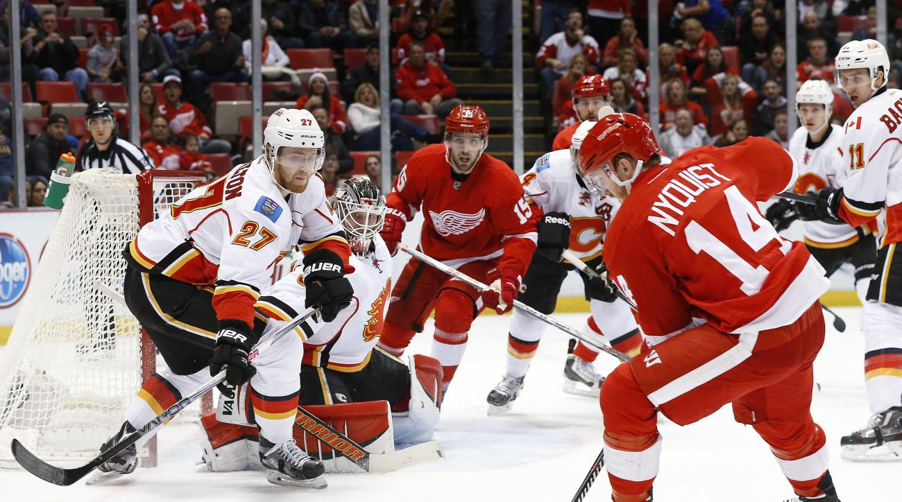 Detroit Red Wings center Gustav Nyquist (14) shoots on Calgary Flames defenseman Dougie Hamilton (27) in the second period of an NHL hockey game, Sunday, Dec. 20, 2015 in Detroit. (AP Photo/Paul Sancya)