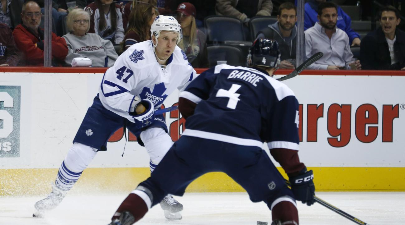 Toronto Maple Leafs center Leo Komarov, back, of Estonia, pursues the puck as Colorado Avalanche defenseman Tyson Barrie watches during the second period of an NHL hockey game Monday, Dec. 21, 2015, in Denver. (AP Photo/David Zalubowski)