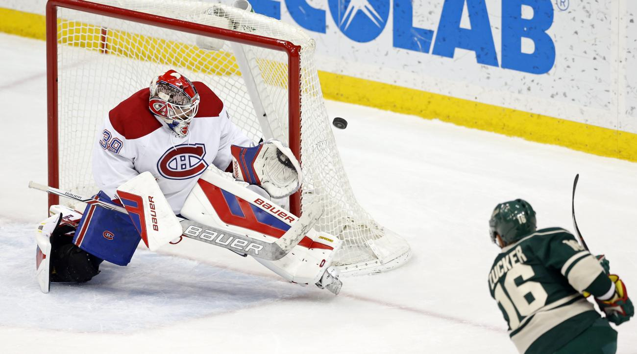 Montreal Canadiens goalie Mike Condon, left, stops a shot by Minnesota Wild's Jason Zucker, right, in the first period of an NHL hockey game, Tuesday, Dec. 22, 2015, in St. Paul, Minn. (AP Photo/Jim Mone)