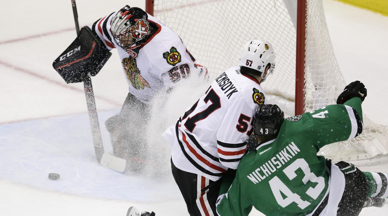 Chicago Blackhawks goalie Corey Crawford (50) and defenseman Trevor van Riemsdyk (57) defend the goal against Dallas Stars right wing Valeri Nichushkin (43) during the second period of an NHL hockey game Tuesday, Dec. 22, 2015, in Dallas. (AP Photo/LM Ote