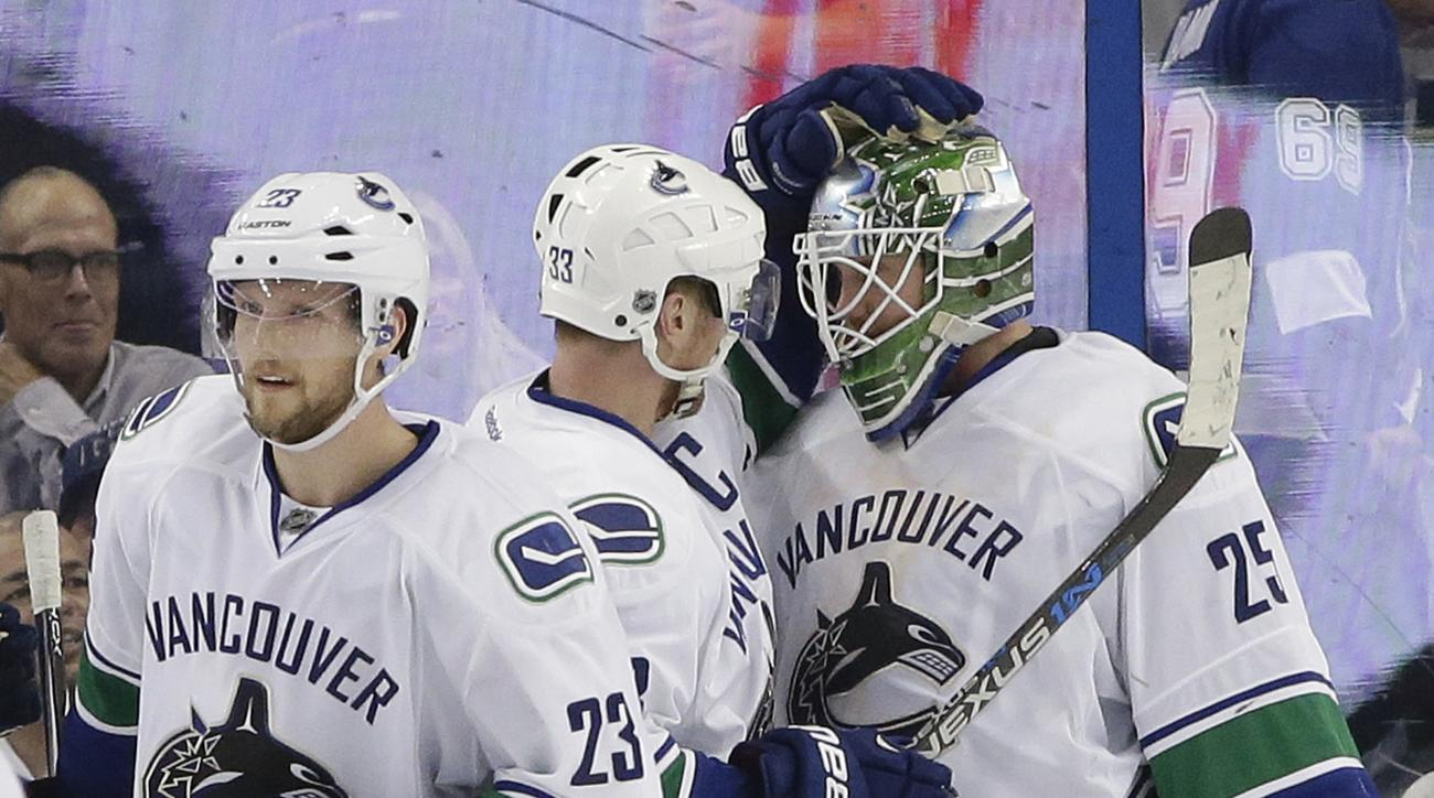 Vancouver Canucks goalie Jacob Markstrom (25), of Sweden, celebrates with center Henrik Sedin (33), of Sweden, and defenseman Alexander Edler (23) after the team defeated the Tampa Bay Lightning 2-1 in an NHL hockey game Tuesday, Dec. 22, 2015, in Tampa,
