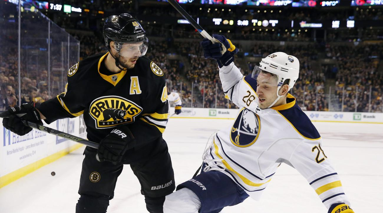 Boston Bruins' David Krejci (46) checks Buffalo Sabres' Zemgus Girgensons (28) during the first period of an NHL hockey game in Boston, Saturday, Dec. 26, 2015. (AP Photo/Michael Dwyer)
