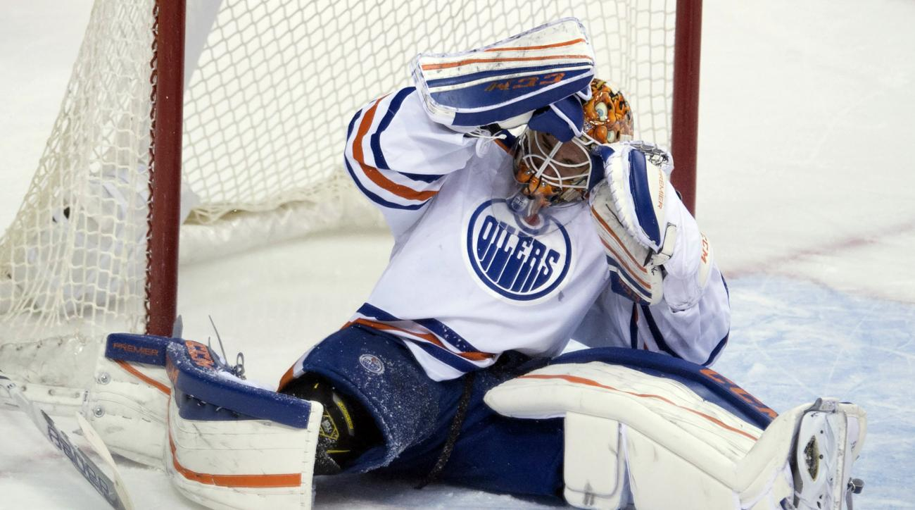 Edmonton Oilers goalie Cam Talbot (33) reacts to hitting the net in a collision during third period of an NHL hockey game against the Edmonton Oilers, Saturday, Dec. 26, 2015, in Vancouver, British Columbia. (Jonathan Hayward/The Canadian Press via AP) MA