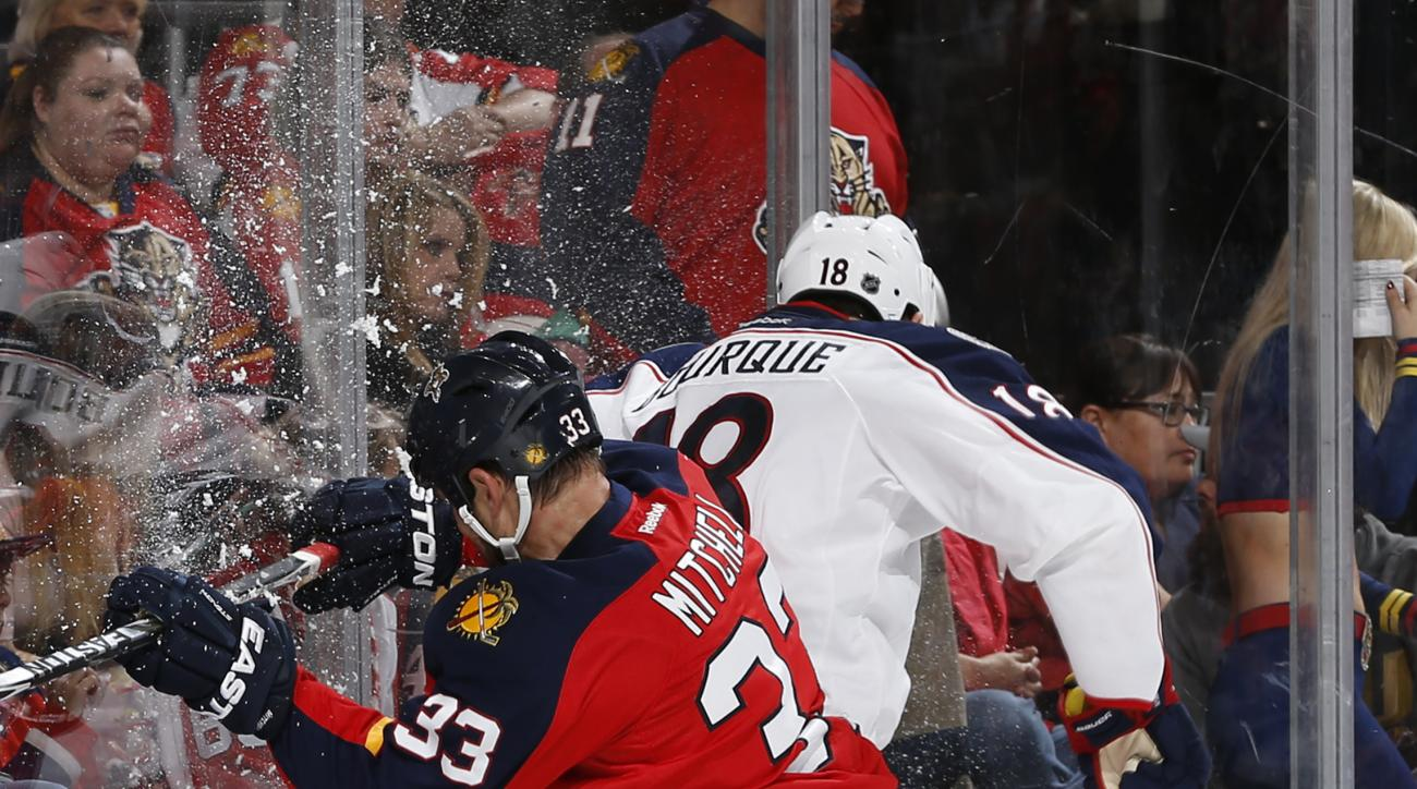 Florida Panthers defenseman Willie Mitchell (33) checks Columbus Blue Jackets forward Rene Bourque (18) into the boards during the second period of an NHL hockey game, Sunday, Dec. 27, 2015, in Sunrise, Fla. (AP Photo/Joel Auerbach)