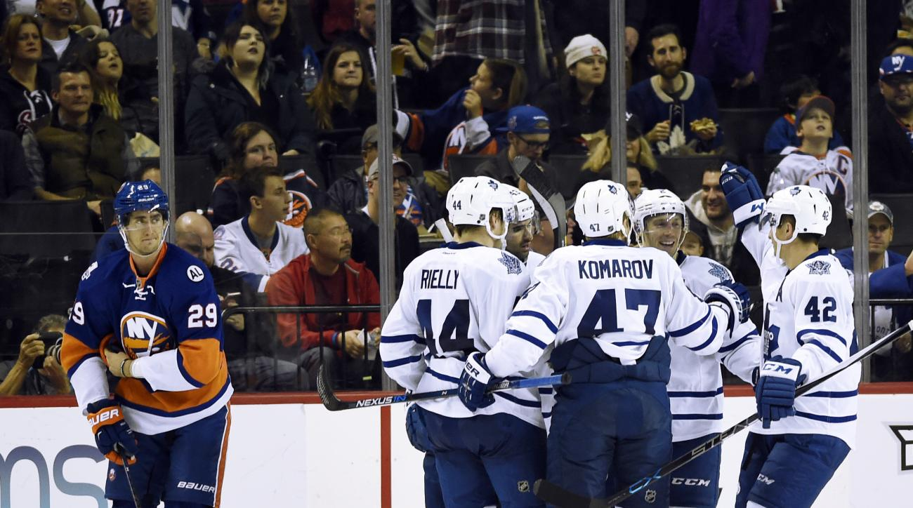 Toronto Maple Leafs defenseman Morgan Rielly (44), center Leo Komarov (47) and  center Tyler Bozak (42) celebrate right wing Michael Grabner's goal with teammates as New York Islanders center Brock Nelson (29) reacts during the second period of an NHL hoc