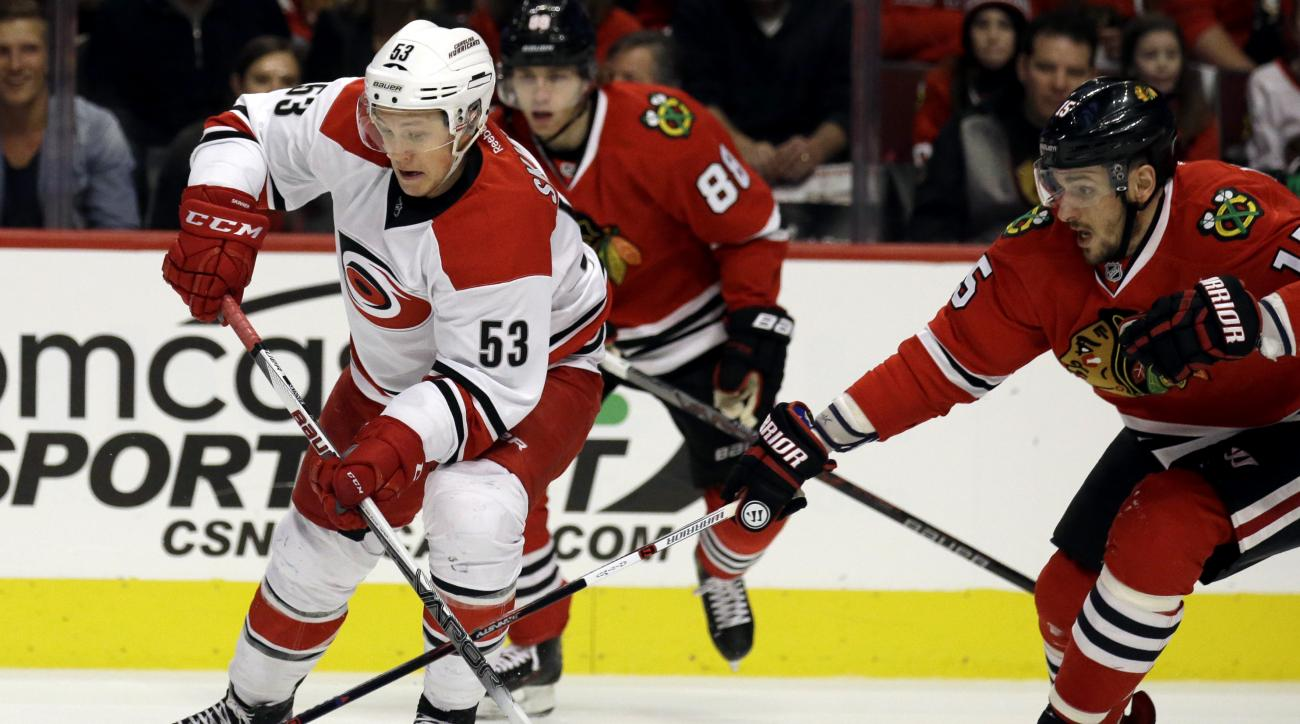 Carolina Hurricanes left wing Jeff Skinner, left, controls the puck against Chicago Blackhawks center Artem Anisimov during the first period of an NHL hockey game Sunday, Dec. 27, 2015, in Chicago. (AP Photo/Nam Y. Huh)