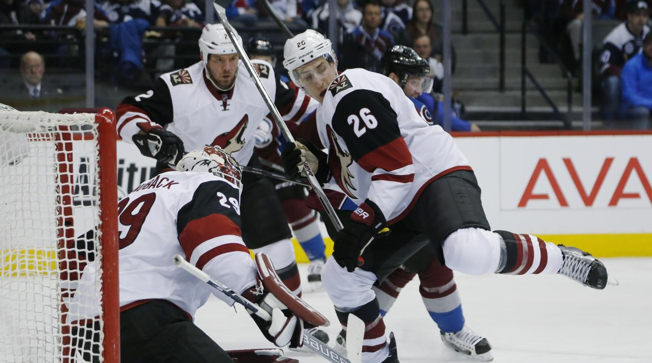 Arizona Coyotes goalie Anders Lindback (29), front, left, of Sweden, stops shot as defenseman Michael Stone, front right, pursues the puck while checking Colorado Avalanche center Matt Duchene, back, right, in the first period of an NHL hockey game Sunday