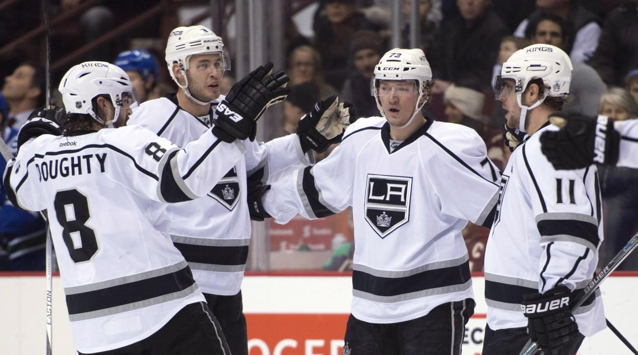 Los Angeles Kings center Tyler Toffoli (73) celebrates his goal against the Los Angeles Kings with his teammates Drew Doughty (8) Brayden McNabb (3) and Anze Kopitar (11) during the first period of an NHL hockey game Monday, Dec. 28, 2015, in Vancouver, B