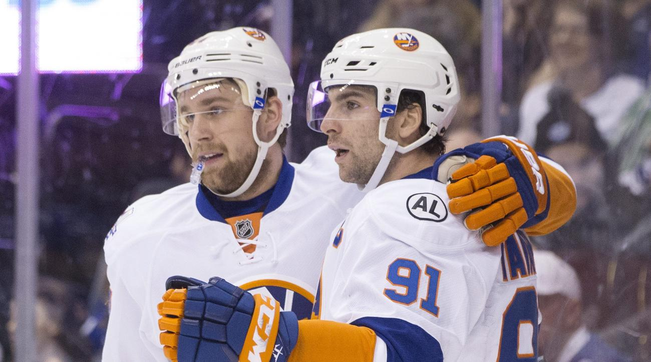 New York Islanders' John Tavares, right, celebrates with teammate Calvin de Haan after scoring against the Toronto Maple Leafs during the first period of an NHL hockey game in Toronto, Tuesday, Dec. 29, 2015.  (Chris Young/The Canadian Press via AP) MANDA