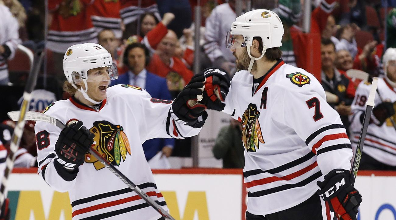Chicago Blackhawks' Brent Seabrook (7) celebrates his goal against the Arizona Coyotes with Patrick Kane, left, during the first period of an NHL hockey game Tuesday, Dec. 29, 2015, in Glendale, Ariz. (AP Photo/Ross D. Franklin)