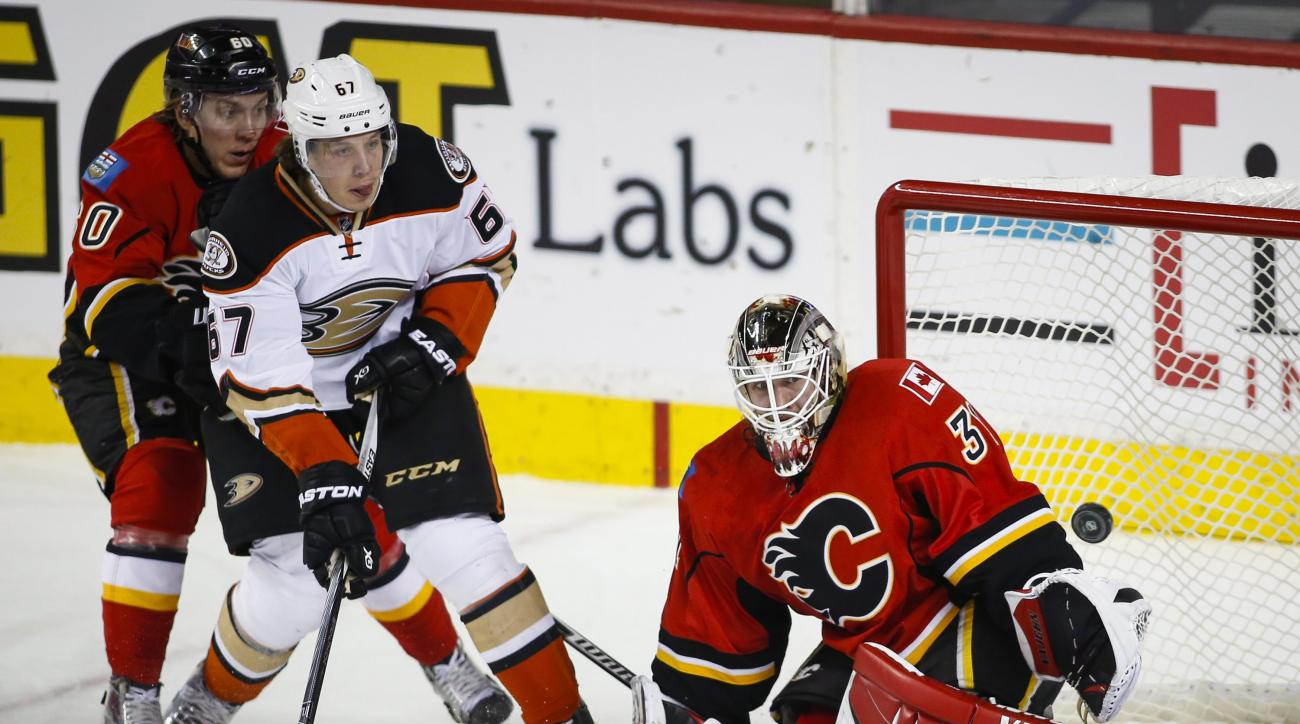 Anaheim Ducks' Rickard Rakell, center, watches as his shot go past Calgary Flames' goalie Karri Ramo, right, as Markus Granlund, looks on during the third period of an NHL hockey game in Calgary, Alberta, Tuesday, Dec. 29, 2015. (Jeff McIntosh/The Canadia
