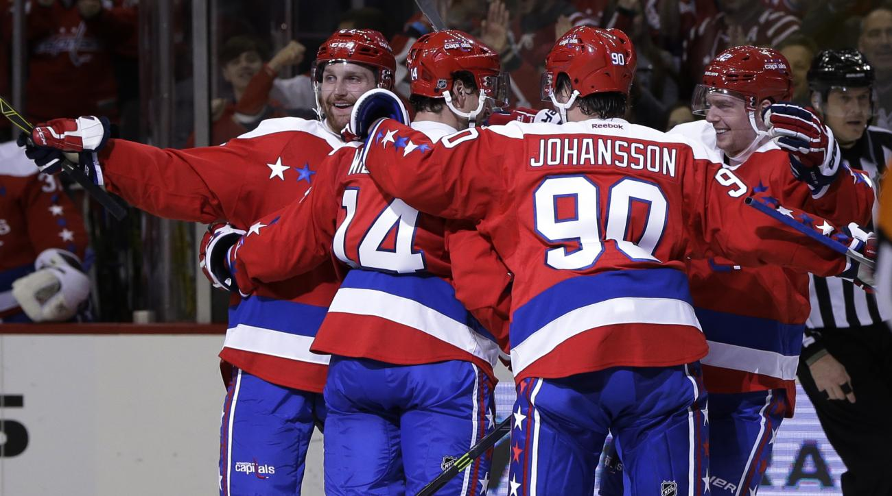 Washington Capitals right wing Justin Williams (14) celebrates his goal with teammates Marcus Johansson (90), Karl Alzner (27), and  Evgeny Kuznetsov (92) during the second period of an NHL hockey game against the Buffalo Sabres, Wednesday, Dec. 30, 2015,