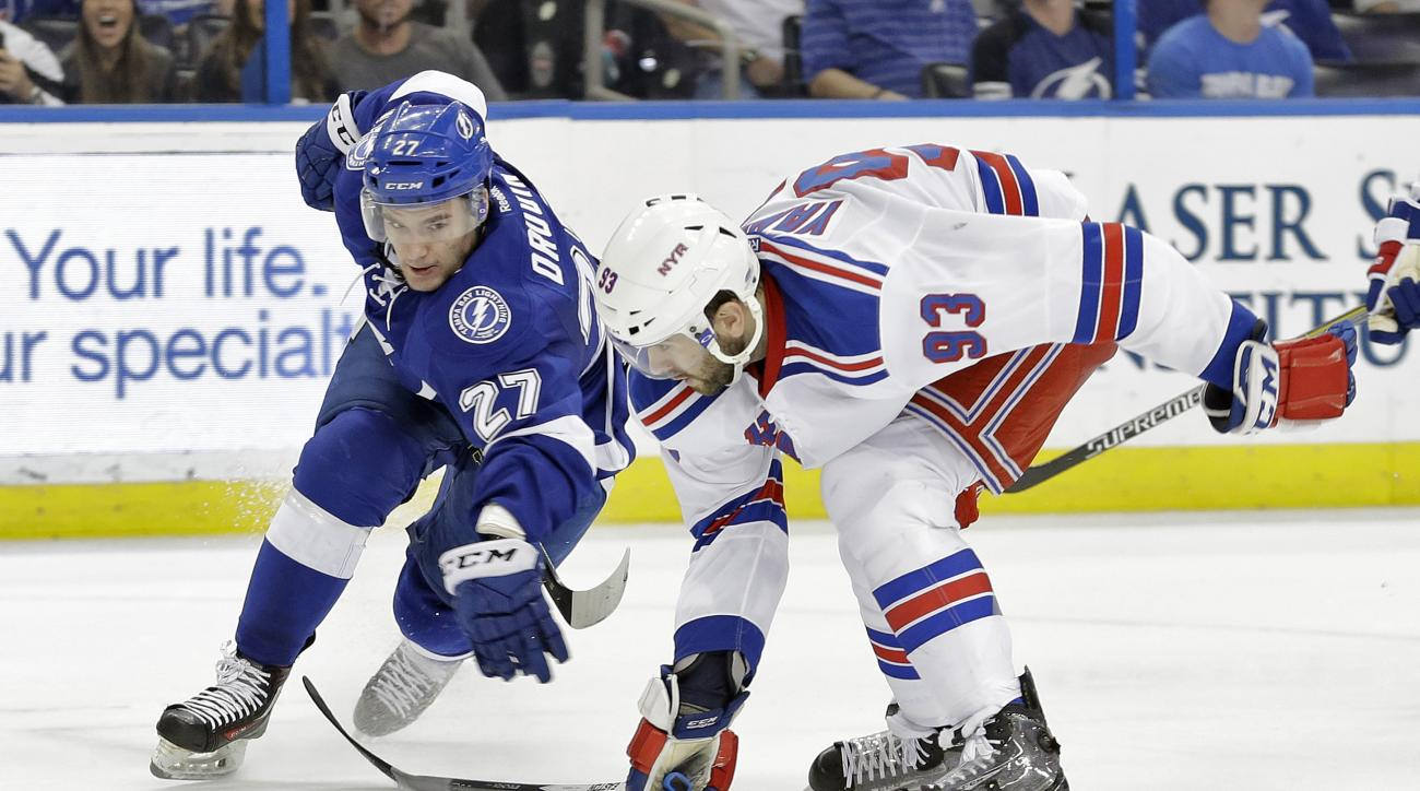 Tampa Bay Lightning left wing Jonathan Drouin (27) is knocked off the puck by New York Rangers defenseman Keith Yandle (93) during the second period of an NHL hockey game Wednesday, Dec. 30, 2015, in Tampa, Fla. (AP Photo/Chris O'Meara)