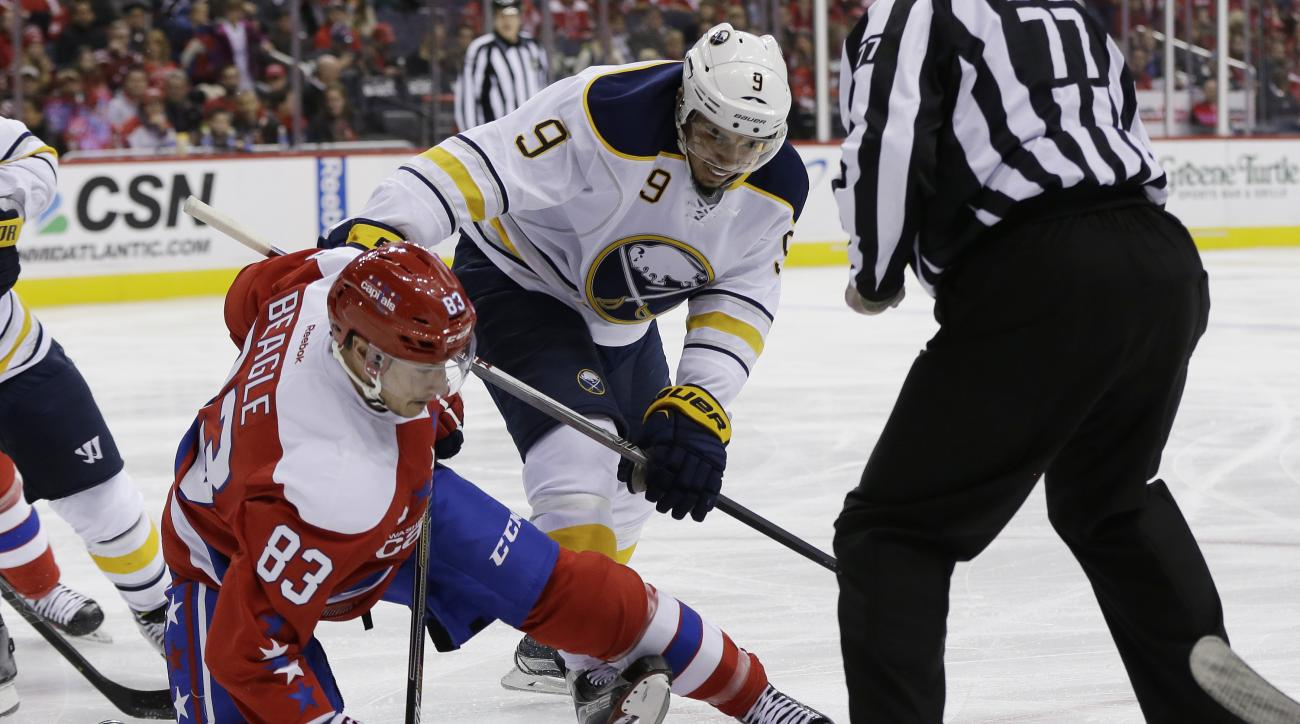 Washington Capitals center Jay Beagle (83) and Buffalo Sabres left wing Evander Kane (9) compete on a face-off after linesman Tim Nowak (77) dropped the puck during the first period of an NHL hockey game Wednesday, Dec. 30, 2015, in Washington. The Washin