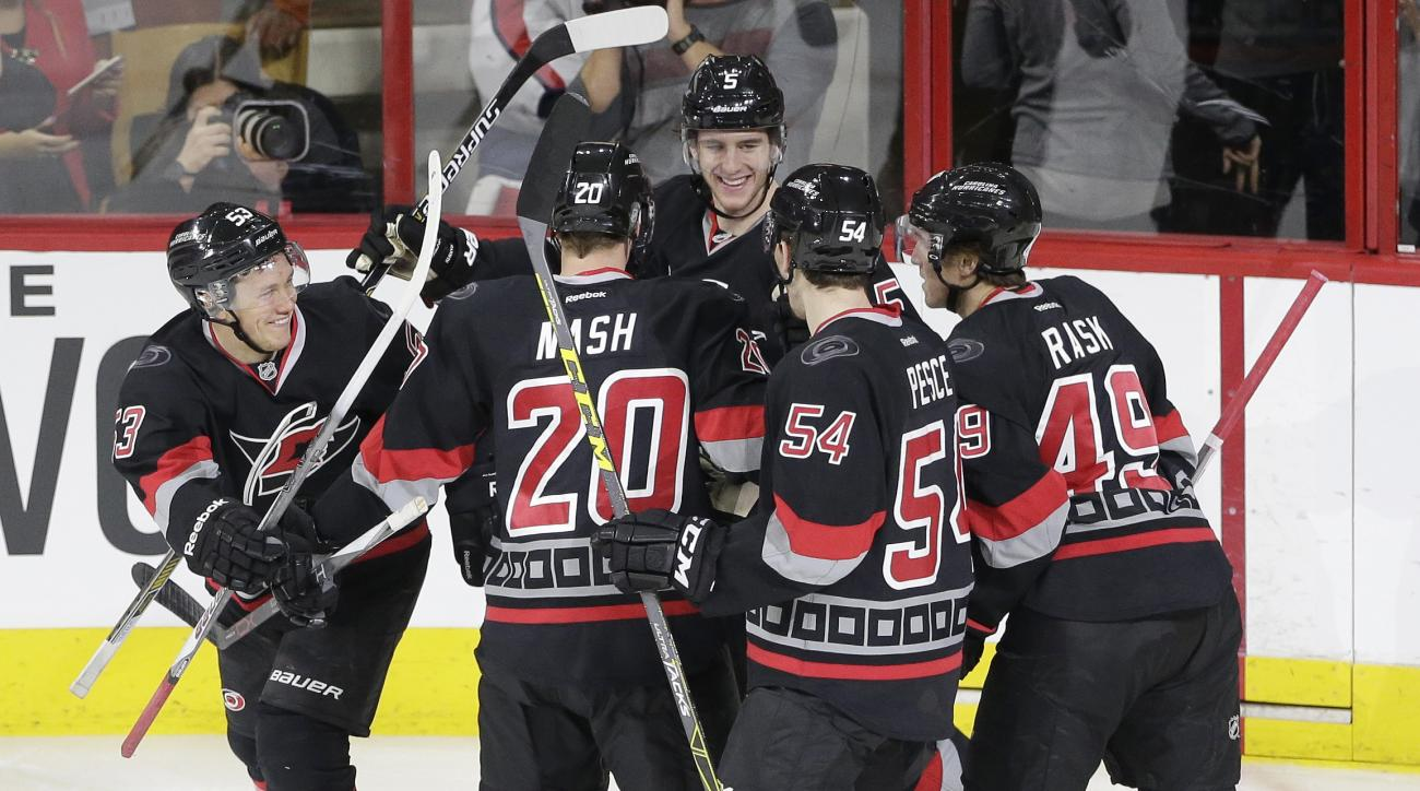 Carolina Hurricanes' Jeff Skinner (53) celebrates his goal against the Washington Capitals with teammates Riley Nash (20), Brett Pesce (54), Noah Hanifin (5) and Victor Rask (49), of Sweden, during the third period of an NHL hockey game in Raleigh, N.C.,