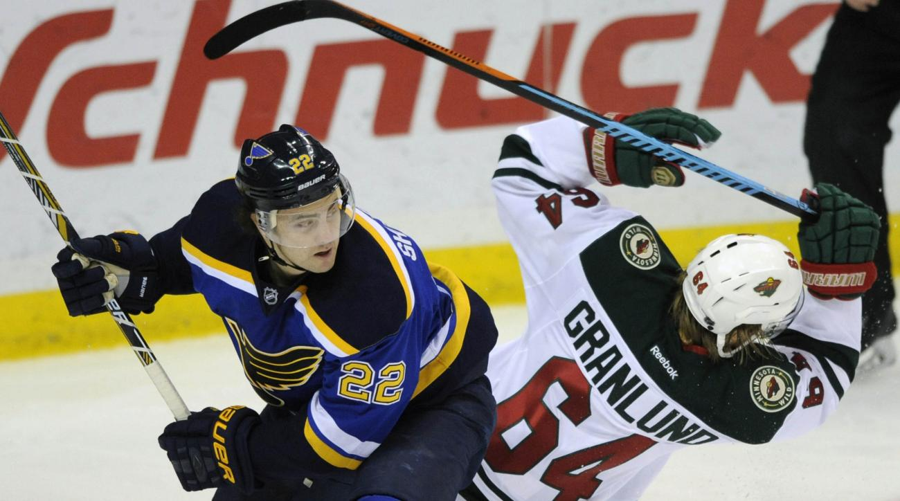 Minnesota Wild's Mikael Granlund (64), of Finland, is checked by St. Louis Blues' Kevin Shattenkirk (22) during the second period of an NHL hockey game, Thursday, Dec. 31, 2015, in St. Louis. (AP Photo/Bill Boyce)