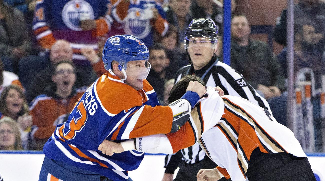 Anaheim Ducks' Kevin Bieksa (2) and Edmonton Oilers' Matt Hendricks (23) fight during the second period of an NHL hockey game in Edmonton, Alberta, Wednesday, Dec. 31, 2015. (Jason Franson/The Canadian Press via AP) MANDATORY CREDIT