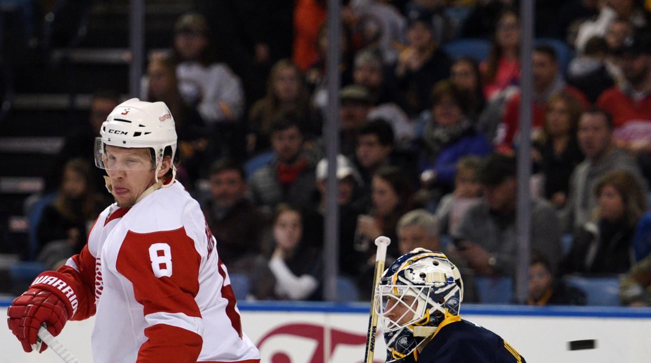 Detroit Red Wings left winger Justin Abdelkader (8) deflects the puck on Buffalo Sabres goaltender Chad Johnson, right, during the second period of an NHL hockey game, Saturday Jan. 2, 2016 in Buffalo, N.Y. (AP Photo/Gary Wiepert)