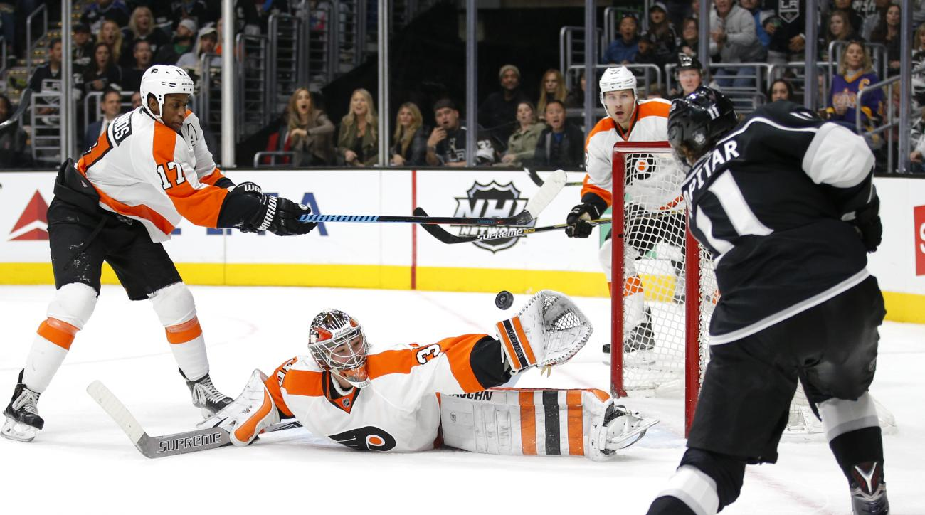 Philadelphia Flyers goalie Michal Neuvirth, of the Czech Republic, center, stops a shot by Los Angeles Kings' Anze Kopitar, right, of Slovenia, during the second period of an NHL hockey game, Saturday, Jan. 2, 2016, in Los Angeles. At left is Flyers' Wayn