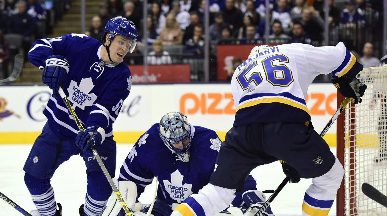 Toronto Maple Leafs goalie Jonathan Bernier makes a save on St. Louis Blues' Magnus Paajarvi (56) as Maple Leafs' Jake Gardiner (51) defends during the third period of an NHL hockey game in Toronto on Saturday, Jan. 2, 2016. (Frank Gunn/The Canadian Press