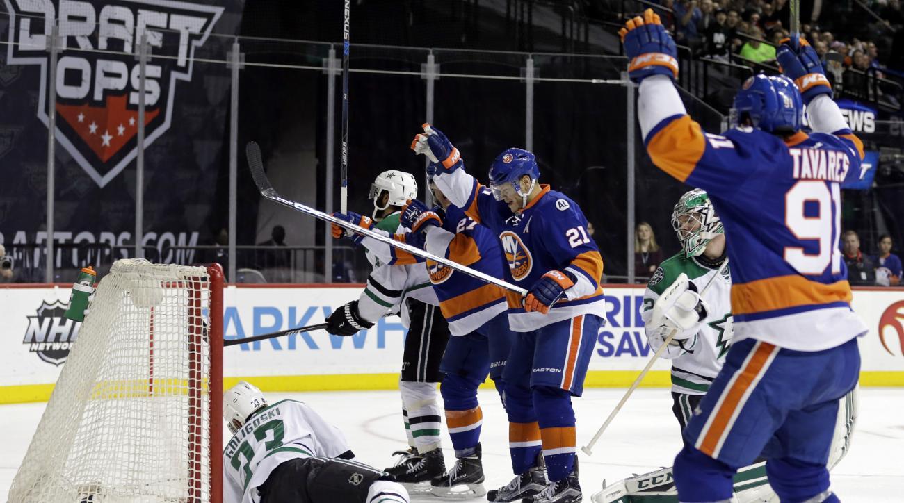 New York Islanders right wing Kyle Okposo (21) celebrates scoring a goal past Dallas Stars defenseman Alex Goligoski (33) and goalie Kari Lehtonen in the second period of an NHL hockey game Sunday, Jan. 3, 2016, in New York. (AP Photo/Adam Hunger)