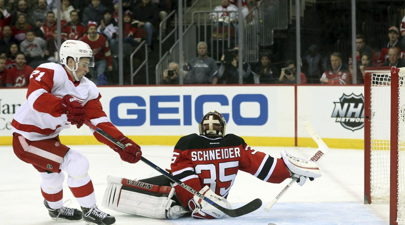 Detroit Red Wings center Dylan Larkin (71) shoots the puck for a goal behind New Jersey Devils goalie Cory Schneider (35) during the first period of an NHL hockey game Monday, Jan. 4, 2016, in Newark, N.J. (AP Photo/Mel Evans)