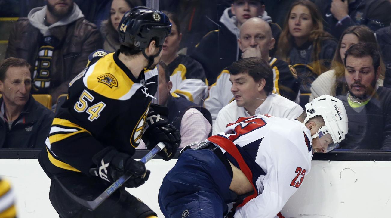 Boston Bruins' Adam McQuaid (54) checks Washington Capitals' Zach Sill (23) during the first period of an NHL hockey game in Boston, Tuesday, Jan. 5, 2016. (AP Photo/Michael Dwyer)