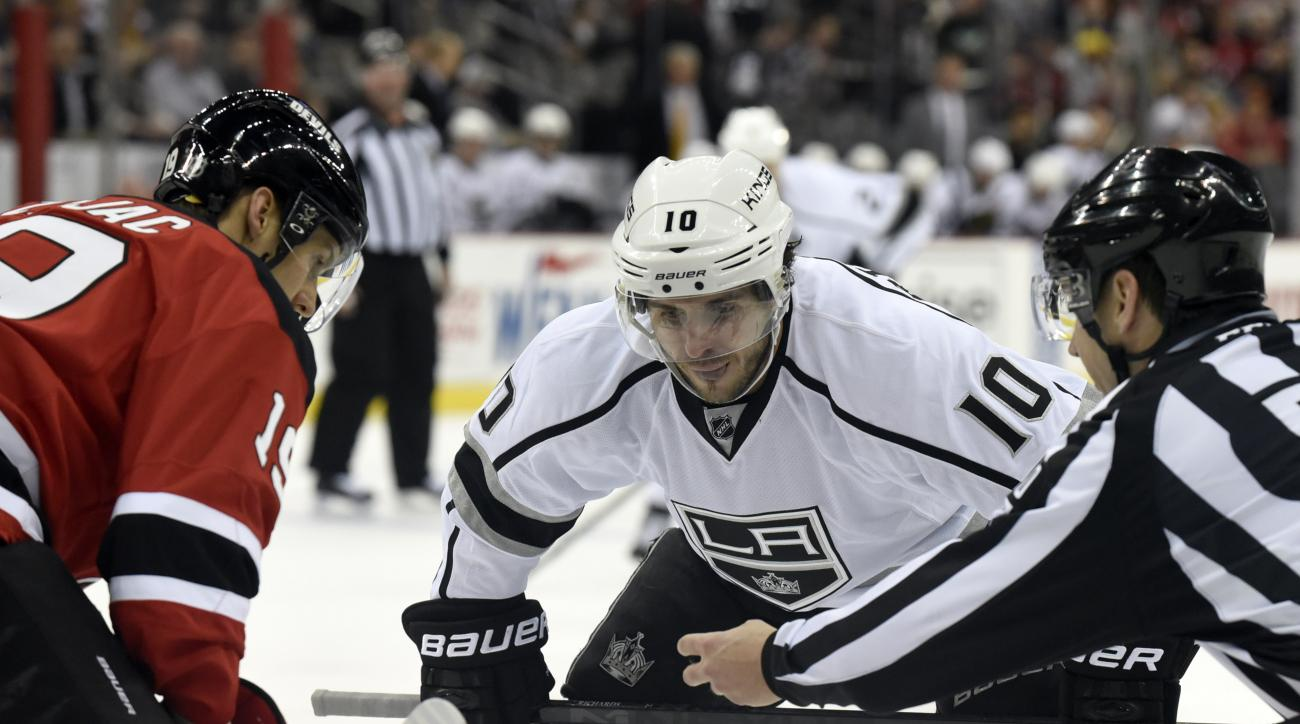Los Angeles Kings' Mike Richards (10) prepares to take a face-off against New Jersey Devils' Travis Zajac during the first period of an NHL hockey game Monday, March 23, 2015, in Newark, N.J. (AP Photo/Bill Kostroun)