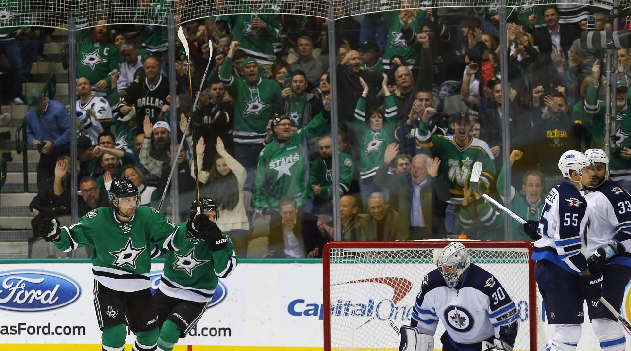Dallas Stars' Patrick Sharp (10) and Mattias Janmark (13) celebrate after a goal against Winnipeg Jets goalie Connor Hellebuyck as Mark Scheifele (55) and Dustin Byfuglien (33) are near during the first period of an NHL hockey game, Thursday, Jan. 7, 2016