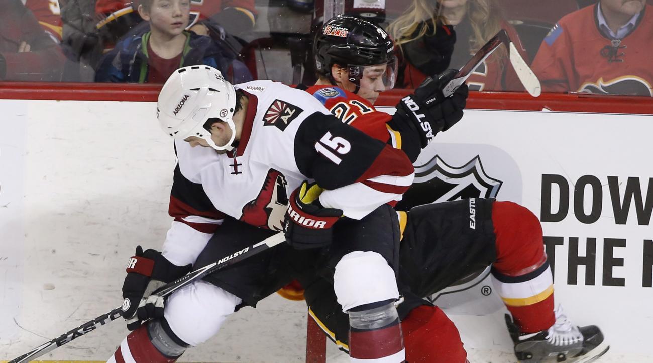 Arizona Coyotes' Boyd Gordon, left, checks Calgary Flames' Mason Raymond off the puck during the second period of an NHL hockey game Thursday, Jan. 7, 2015, in Calgary, Alberta. (Larry MacDougal/The Canadian Press via AP)
