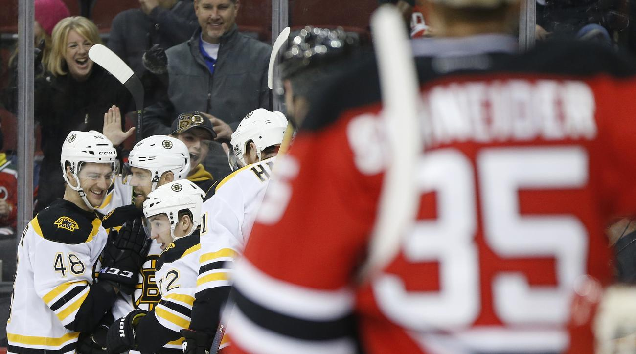 Boston Bruins players celebrate a goal by Frank Vatrano, third from left, as New Jersey Devils goalie Cory Schneider (35) looks on during the first period of an NHL hockey game, Friday, Jan. 8, 2016, in Newark, N.J. (AP Photo/Julio Cortez)
