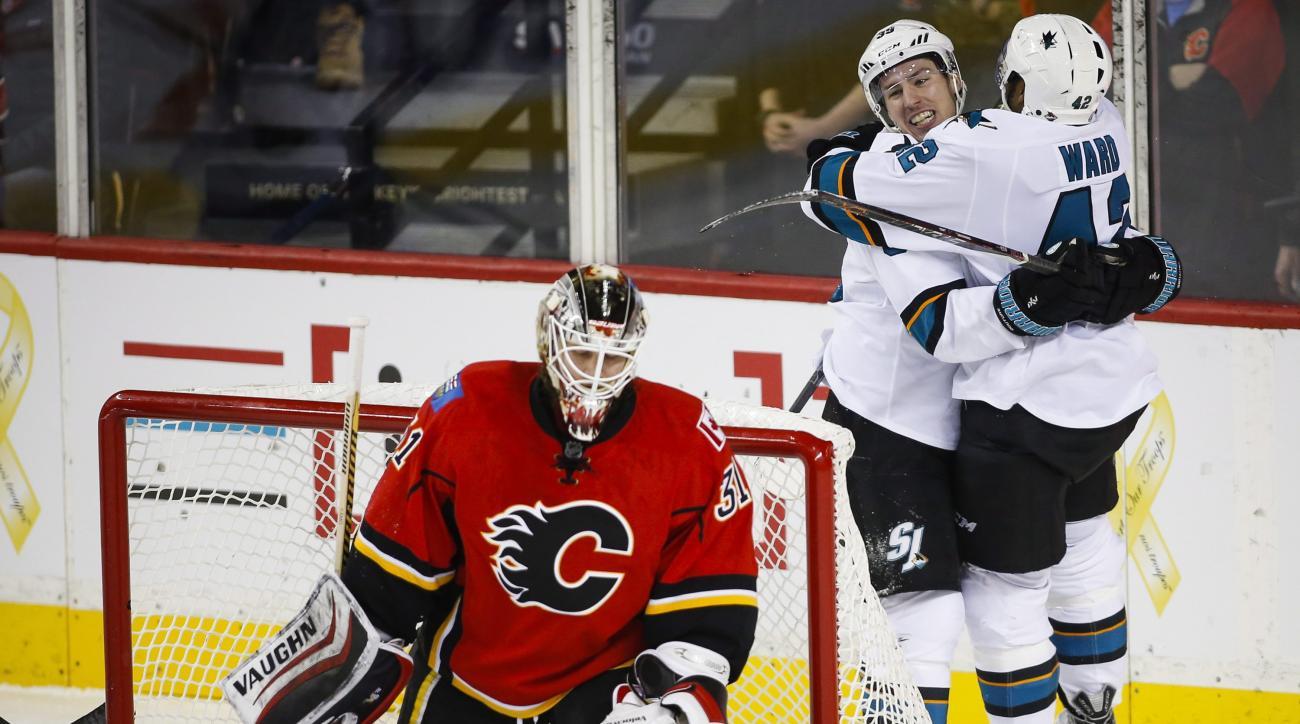 San Jose Sharks' Joel Ward, right, celebrates his goal with teammate Logan Couture, center, as Calgary Flames goalie Karri Ramo, looks away during the third period of an NHL hockey game in Calgary, Alberta, Monday, Jan. 11, 2016. (Jeff McIntosh/The Canadi