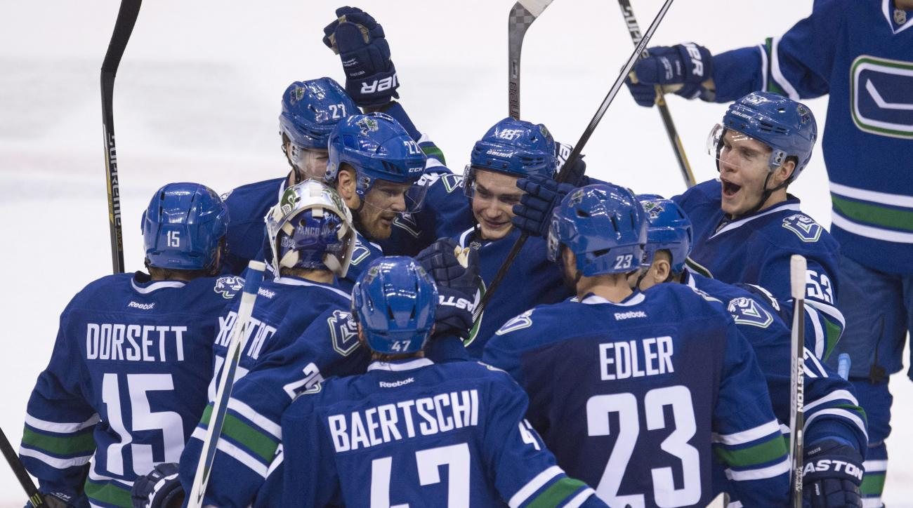 Vancouver Canucks left wing Daniel Sedin (22) celebrates his game-winning goal with his team following overtime in an NHL hockey game in Vancouver, British Columbia, Canada, Monday, Jan. 11, 2016. (Jonathan Hayward/The Canadian Press via AP)