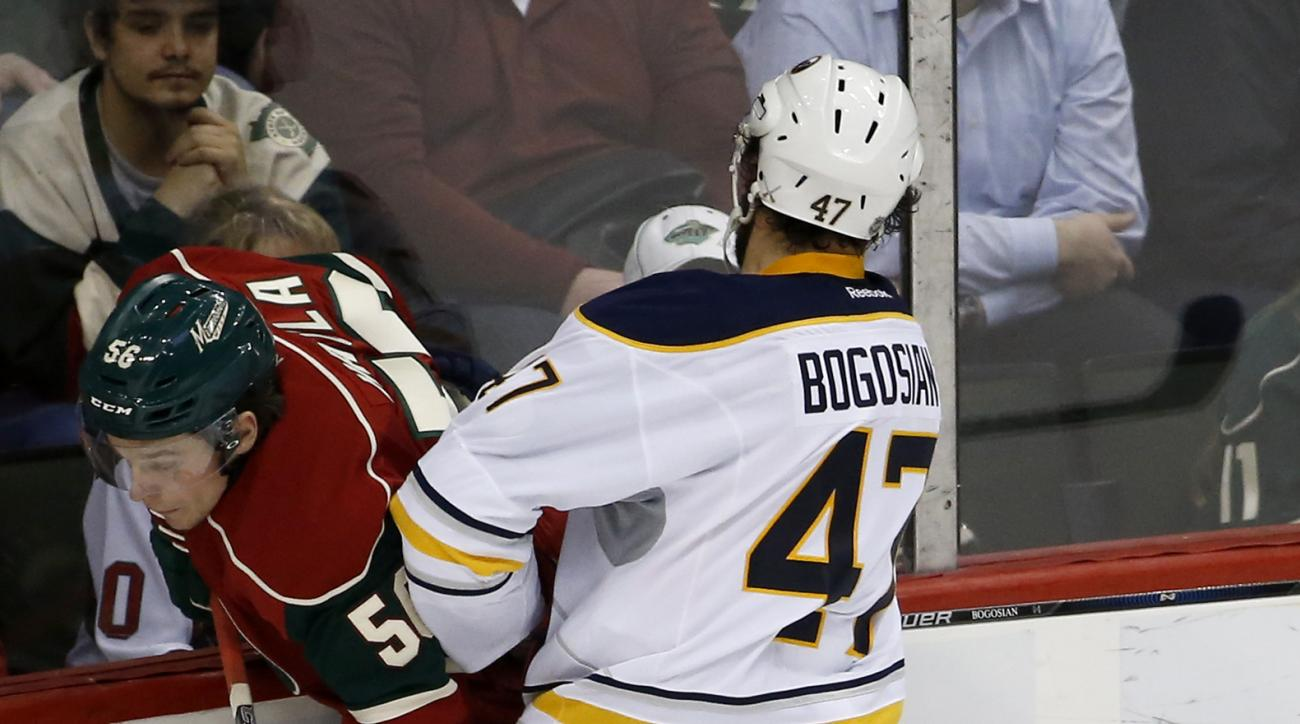 Buffalo Sabres defenseman Zach Bogosian (47) checks Minnesota Wild left wing Erik Haula, left, of Finland, off the puck and into the boards during the first period of an NHL hockey game in St. Paul, Minn., Tuesday, Jan. 12, 2016. (AP Photo/Ann Heisenfelt)