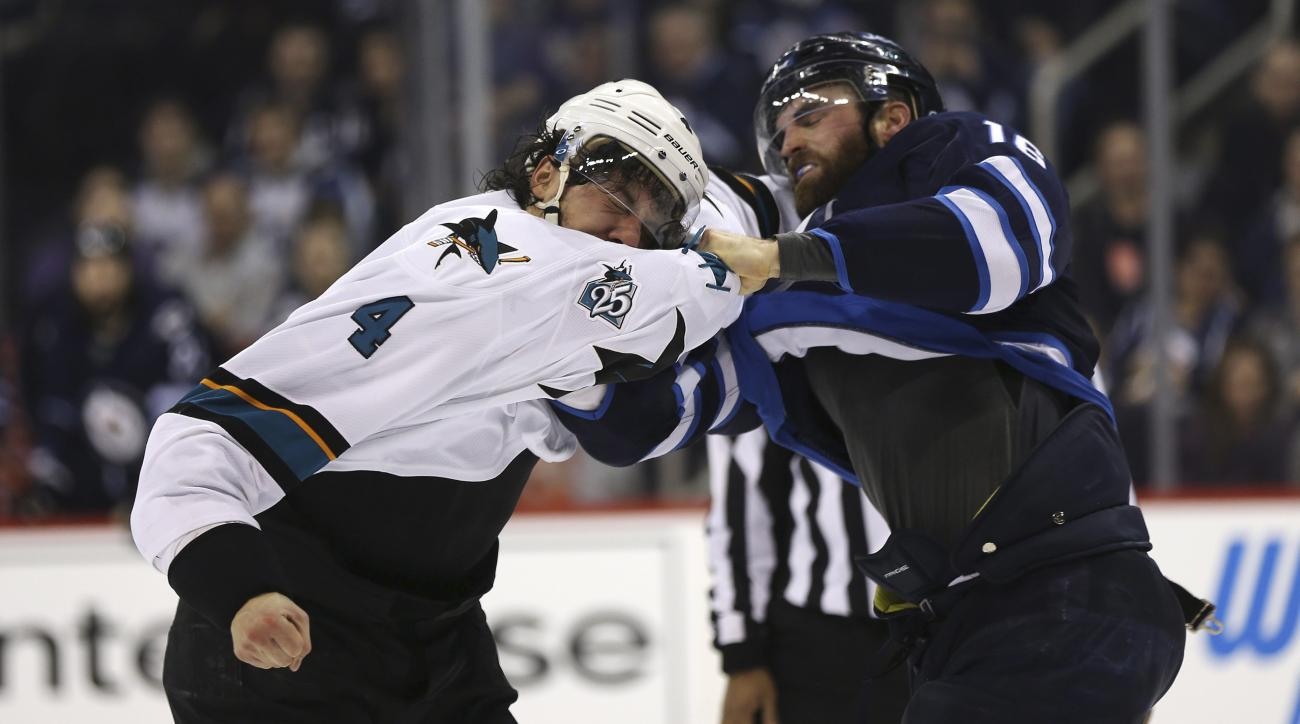 San Jose Sharks' Brenden Dillon (4) fights Winnipeg Jets' Andrew Ladd (16) during the second period of an NHL hockey game Tuesday, Jan. 12, 2016, in Winnipeg, Manitoba. (Trevor Hagan/The Canadian Press via AP)