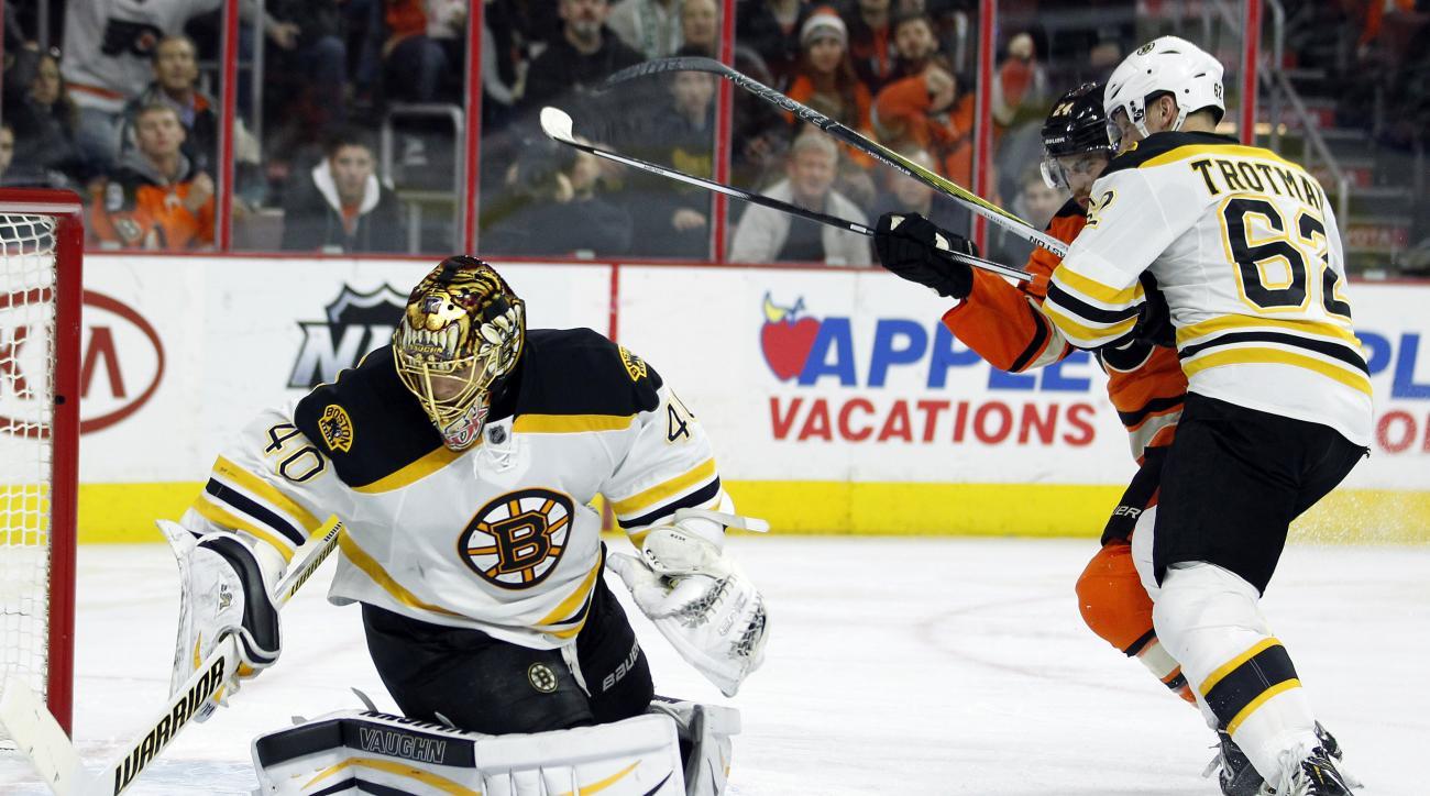 Boston Bruins goalie Tuukka Rask moves to cover the puck while Bruins' Zach Trotman, right, keeps Philadelphia Flyers' Matt Read away during the second period of an NHL hockey game Wednesday, Jan 13, 2016, in Philadelphia.  (AP Photo/Tom Mihalek)