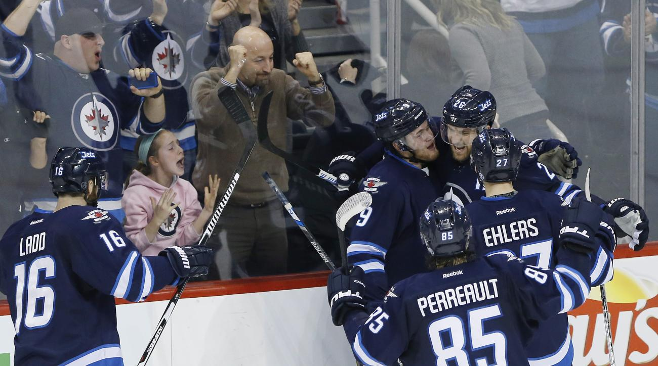 Winnipeg Jets' Andrew Ladd (16), Andrew Copp (9), Mathieu Perreault (85), Blake Wheeler (26) and Nikolaj Ehlers (27) celebrate Wheeler's goal during overtime against the Nashville Predators on Thursday, Jan. 14, 2016, in Winnipeg, Manitoba. (John Woods/Th