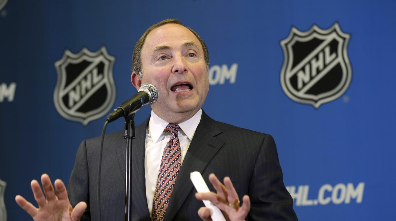 FILE - In this Dec. 8, 2014, file photo, NHL hockey commissioner Gary Bettman speaks to the media after attending an NHL owners meeting in Boca Raton, Fla. The NHL has joined other professional leagues in mandating domestic violence, sexual assault and se