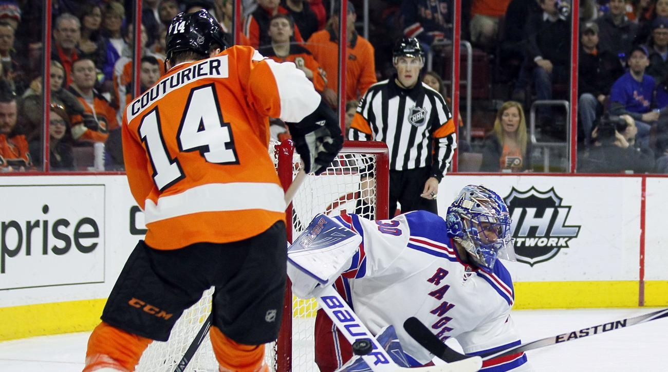 Philadelphia Flyers' Sean Couturier, left, looks to get at the loose puck deflectED from the net by New York Rangers' Henrik Lundqvist during the second period of an NHL hockey game Saturday, Jan 16, 2016,  in Philadelphia. (AP Photo/Tom Mihalek)