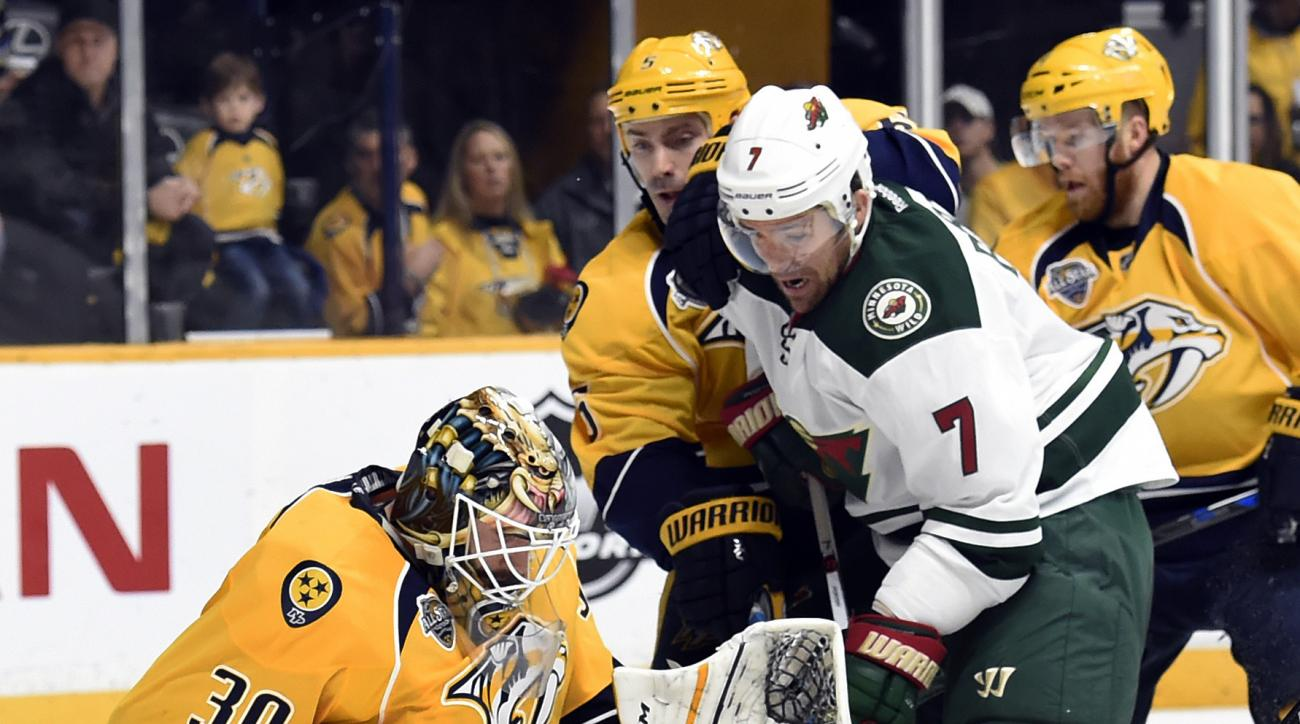 Nashville Predators goalie Carter Hutton (30) stops a shot by Minnesota Wild left wing Chris Porter (7) during the first period of an NHL hockey game Saturday, Jan. 16, 2016, in Nashville, Tenn. (AP Photo/Mark Zaleski)
