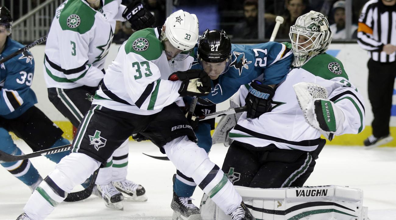 San Jose Sharks' Joonas Donskoi (27) collides with Dallas Stars goalie Antti Niemi, right, and Alex Goligoski (33) during the first period of an NHL hockey game Saturday, Jan. 16, 2016, in San Jose, Calif. (AP Photo/Marcio Jose Sanchez)