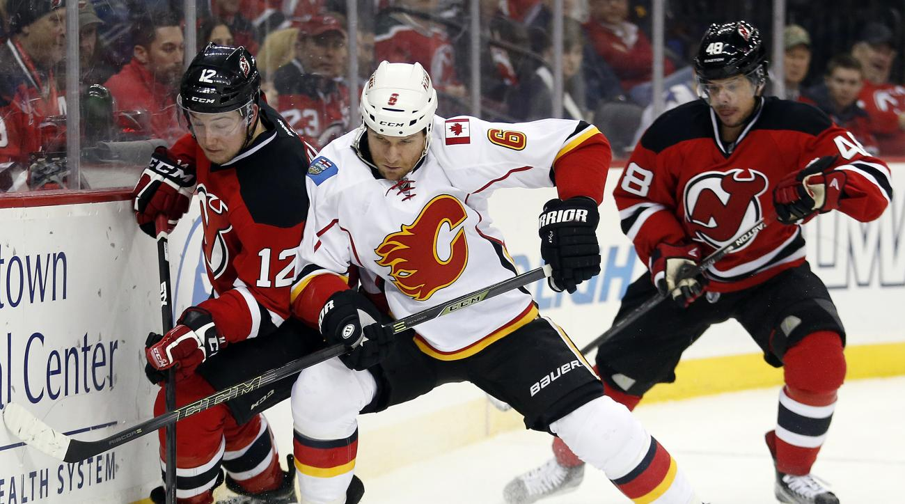 New Jersey Devils center Reid Boucher, left, competes for the puck with Calgary Flames defenseman Dennis Wideman (6) during the second period of an NHL hockey game, Tuesday, Jan. 19, 2016, in Newark, N.J. Devils' Tyler Kennedy, right, looks on during the