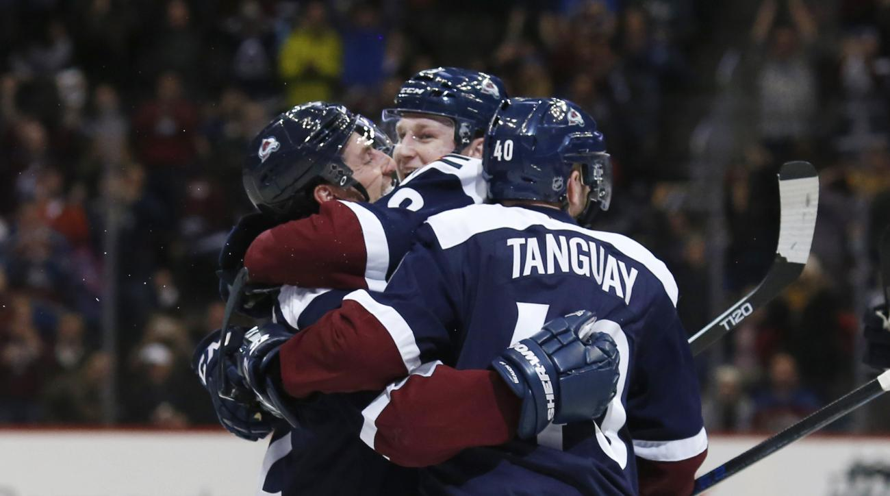 Colorado Avalanche defenseman Francois Beauchemin, left, is congratulated after scoring the go-ahead goal by center Nathan MacKinnon and left wing Alex Tanguay, right, against the Buffalo Sabres late in the third period of an NHL hockey game Wednesday, Ja